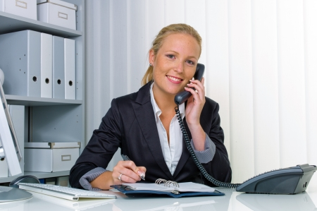 14587337 - a friendly woman phoned at her desk in the office and record dates in the calendar
